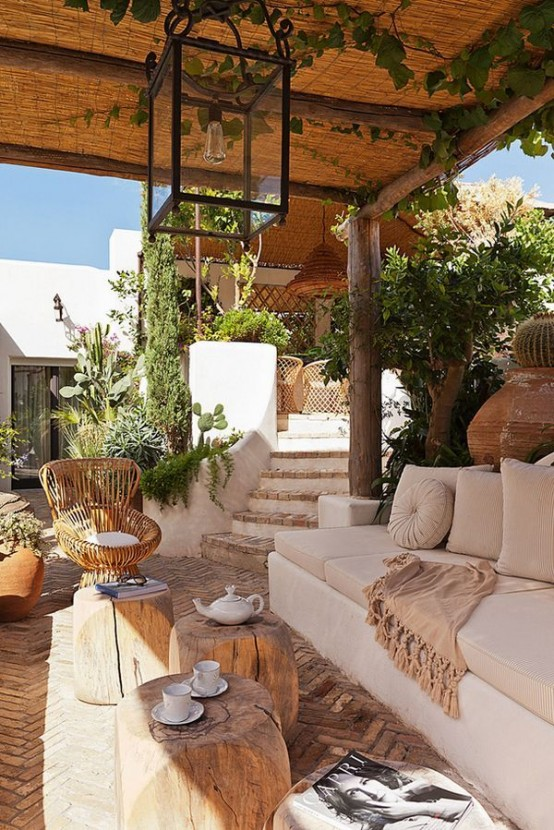 a neutral Mediterranean terrace with neutral furniture, wooden tables, a rattan chair and lots of greenery around