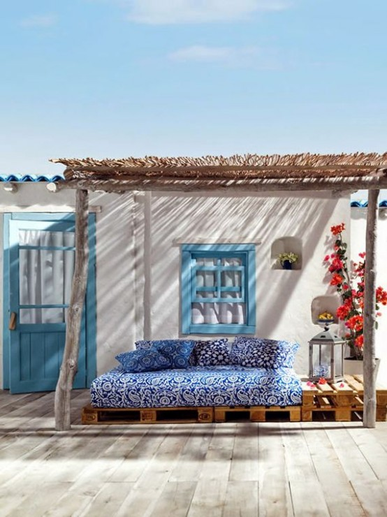 a cheerful Greek summer terrace with pallet furniture, bright blooms and candle lanterns plus bold textiles