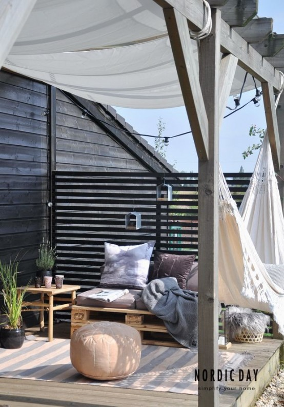 a small Nordic summer terrace with dark walls, pallet and wooden furniture, dusty textiles and a hammock plus ottomans