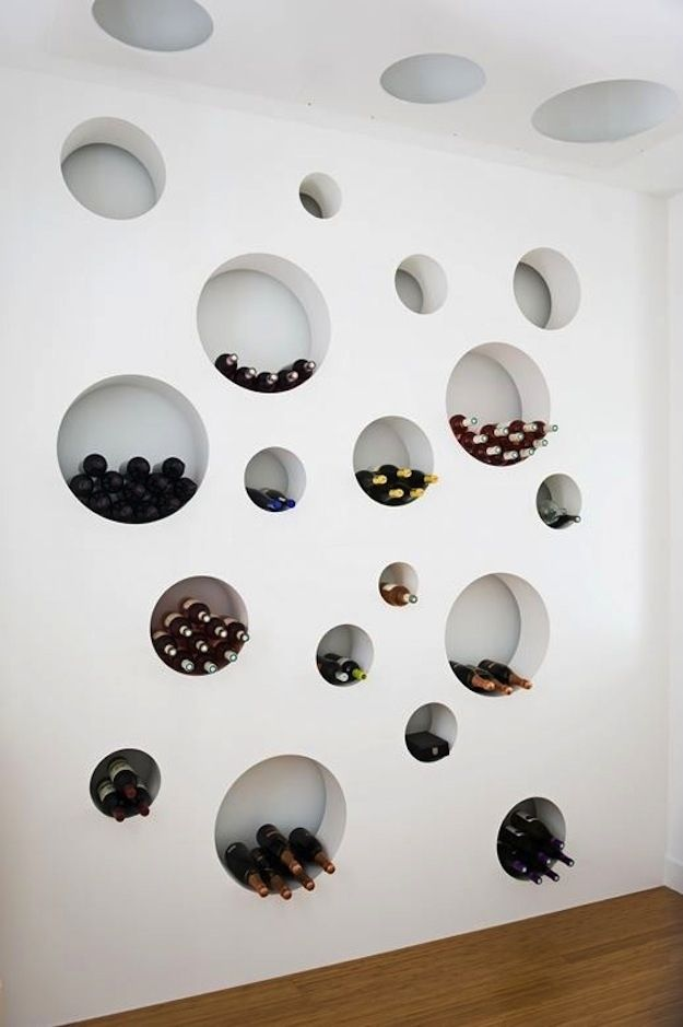 a wall with round cavities that are used to store wine bottles and other stuff is an artwork itself