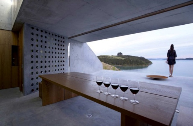 a whole concrete wall with holes is a stylish minimalsit wine storage that will also fit an industrial space