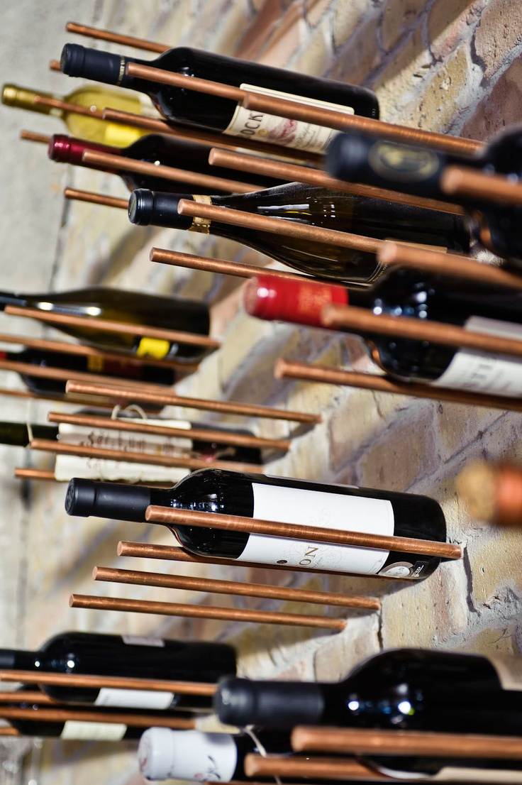 a brick wall with copper metal dowels that are used to hold wine bottles for an industrial kitchen