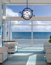 a seaside patio in blues and white, with white furniture, a pendant lamp and blue and white textiles is lovely