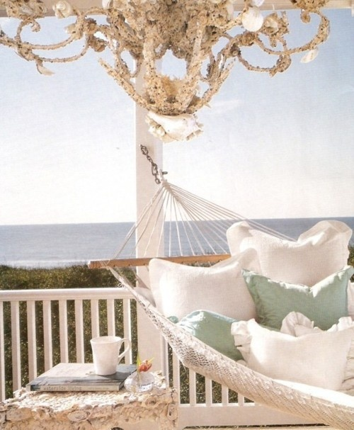 a beachy patio with a hammock and neutral and pastel bedding, with a seashell covered stool and a gorgeous seashell chandelier
