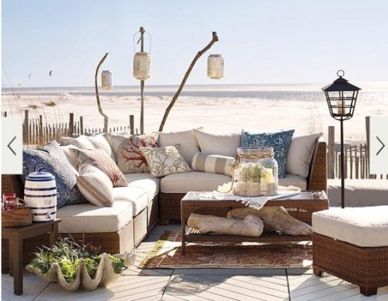 a truly beach patio with wicker furniture, neutral textiles and pillows, potted greenery and succulents and branches with paper lamps plus a gorgeous sea view