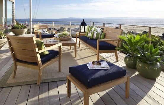 a beachy patio with light-colored wooden furniture, navy upholstery, candle lanterns and potted plants