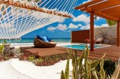a beach deck with a pool, some contemporary furniture, a hammock and a gorgeous sea view