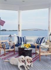 a beachy patio with woven and white wooden furniture, striped navy and white textiles, dark coffee tables, a striped rug and a cool view