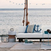 a beach patio with white upholstered furniture, neutral rugs, some rope, seaside pillows and candle lanterns