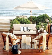 a beach patio with a deck, rich-stained wooden furniture with neutral upholstery, candle lanterns and corals and baskets