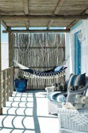 a beachy porch with wicker furniture, a hammock, blue and white textiles and some seashells for decor