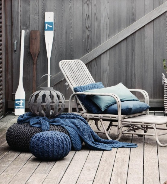 a seaside patio of wood and with a rattan lounger, with blue textiles, crochet ottomans and oars is very cozy