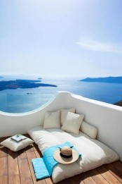 a minimalist seaside deck with a mattress, some pillows and a gorgeous sea view is a lovely space to be