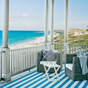 a beach patio with a couple of wicker chairs and a trestle table, printed textiles and a beautiful sea view