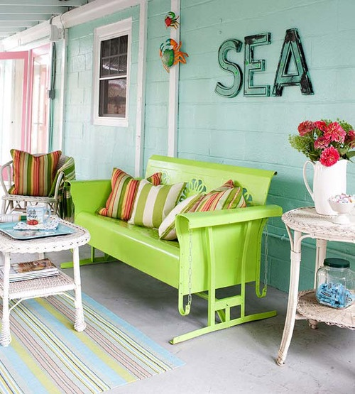a colorful sea porch with mint walls, a neon green bench, colorful textiles, wicker tables and bright blooms