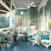 a vintage beach patio with white wicker furniture, striped blue and white upholstery, potted greenery and shutters on the walls