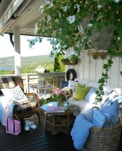 a rustic sea porch with wicker furniture, a bench with white upholstery, bright textiles and potted plants and blooms