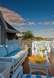 a beach porch with white wicker furniture, blue upholstery, potted plants and blooms and a beautiful sea view