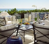 a neutral beach porch with black forged furniture, neutral upholstery, candle lanterns and greenery and blooms