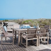 a neutral wooden beach patio with simple furniture, blue tableware and a fantastic sea view