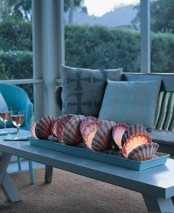 a covered beach patio with white and light blue furniture, blue printed pillows and a unique centerpiece of seashells and candles