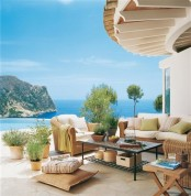 a Mediterranean patio with wicker furniture, a forged table, neutral and pastel bedding and lots of potted greenery
