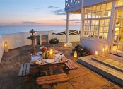 a seaside patio with simple wooden furniture, candle lanterns, blooms and a cool sea view is a very welcoming space