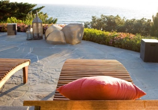 a seaside terrace with a sea view, a couple of loungers, rocks and candle lanterns is a gorgeous place to spend time