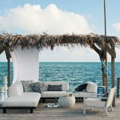 a seaside terrace with neutral upholstered furniture, printed and black pillows and a small roof with grasses