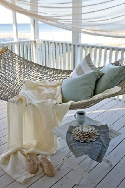 a beachy porch with a hammock, pastel and striped bedding, a stool with a candleholder of seashells and a beach view