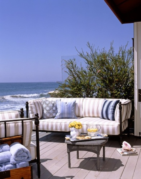 a beachy terrace with a wooden deck, black forged furniture, striped upholstery, a vintage coffee table and a fabulous sea view