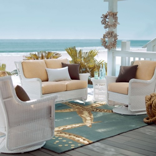 a bright beach terrace with white wicker furniture, neutral upholstery, a printed rug and a beautiful sea view