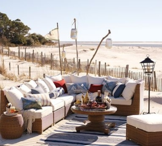 a beach patio with wicker furniture, white upholstery and bright pillows, candle lanterns and a striped rug