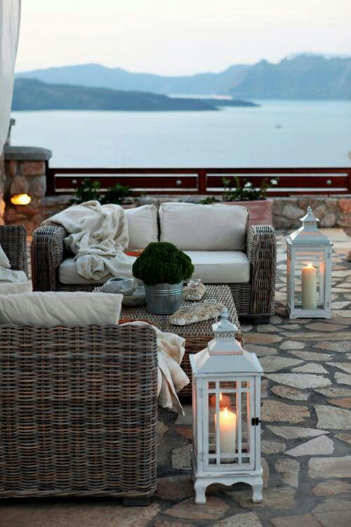 a seaside patio with wicker furniture, neutral upholstery, potted greenery and white candle lanterns features a very lovely view
