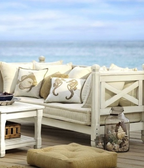 a seaside patio with vintage neutral furniture, neutral upholstery and printed pillows, jars with seashells and crates is very chic