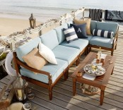 a beach patio with rich-stained wooden furniture and blue upholstery, striped pillows, candle lanterns and seashells and rope for decor