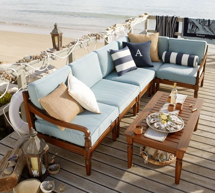 a beach patio with rich stained wooden furniture and blue upholstery, striped pillows, candle lanterns and seashells and rope for decor