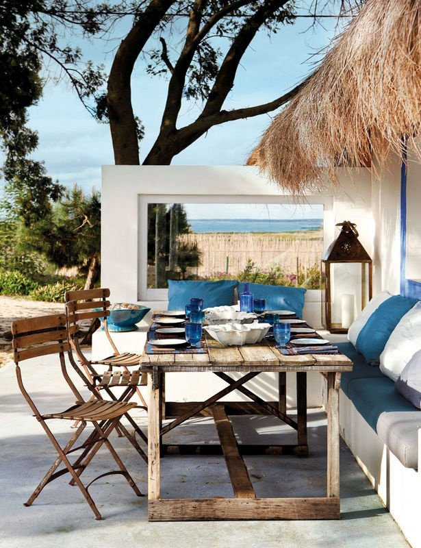 a seaside patio with built in white furniture, white and blue textiles, a vintage wooden table and simple chairs plus candle lanterns