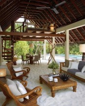 a beach patio under a roof, with beach sand, vintage wooden furniture, neutral upholstery and potted plants