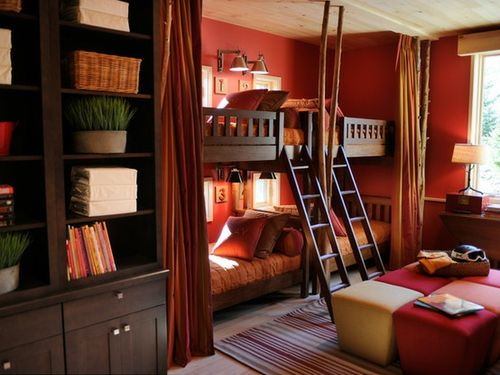 Traditional shared bedroom painted in a bold shade of red. Bunk beds for four kids could be hidden behind curtains for privacy.