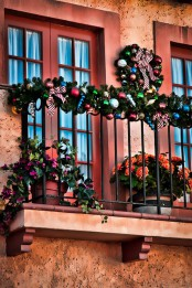 bold blooms in pots and ornaments and greenery garlands and wreaths to decorate the balcony for winter holidays