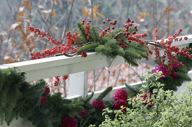 lush greenery, evergreens, berries and red Christmas ornaments to decorate the balcony for the holidays with a natural feel