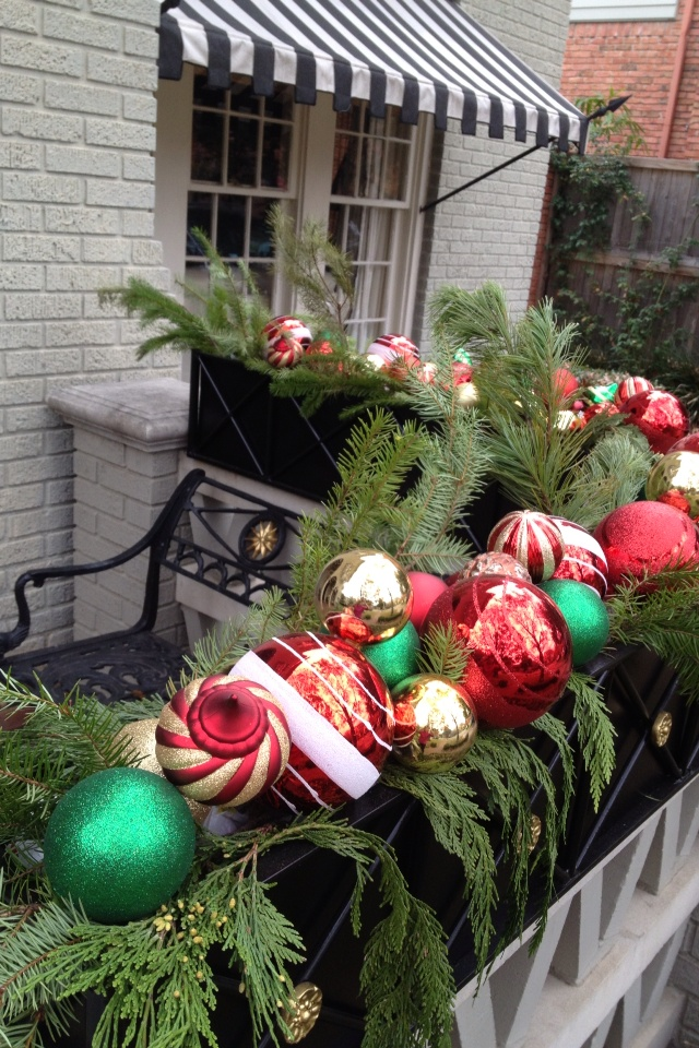 a box with lush evergreens and colorful Christmas ornaments is a great idea for holiday decor