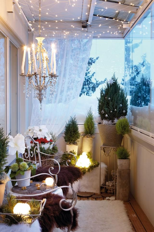 a cozy winter balcony done with mini Christmas trees, lots of faux fur, a crystal chandelier and lots of lights