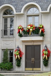 bright holiday balcony decor done with evergreens, oversized gold, green and red ornaments and red bows