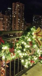 a greenery garland and wreathwith lights and red and gold bows to decorate the balcony for holidays