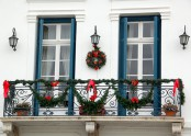 greenery garlands, red bows, a greenery wreath with bows and blue shutters give the balcony a bright holiday look