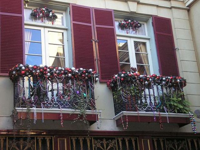 mini balconies decorated with lots of Christmas ornaments, bead garlands, lush foliage and blooms for a strong holiday feel,