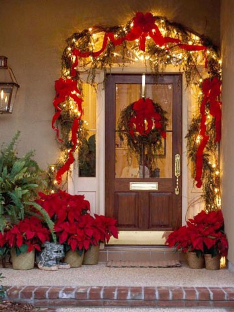 a super bright and bold Christmas porch with red ribbons and bows, lights, a wreath with poinsettias, greenery and poinsettia arrangements in pots