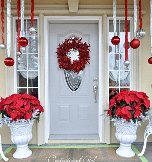 a bright Christmas porch with red and silver ornaments hanging down and poinsettia arrangements plus a red berry wreath on the door is bright and cool